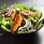 Salad with marinated chicken breast stripes